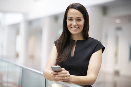 Young woman holding phone in modern university interior