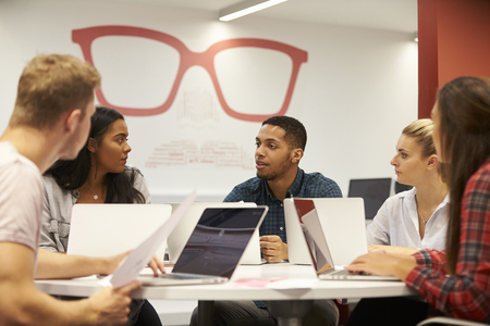 Group Of University Students Collaborating On Project