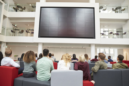 view of an atrium in a building: Students watching big screen in university atrium, back view