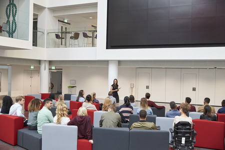 Students at a lecture in university atrium, back view Stock Photo