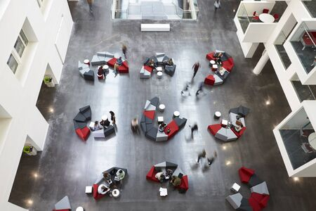 view of an atrium in a building: Overhead view of seating in a university atrium, motion blur