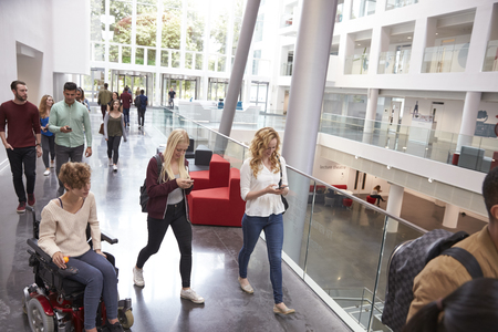 view of an atrium in a building: Students walk and talk using mobile devices in university Stock Photo
