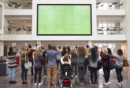 view of an atrium in a building: Students photograph screen with phones, back view full length Stock Photo