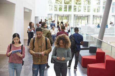 학생들은 태블릿과 휴대 전화를 사용하여 대학 캠퍼스에서 걸어갑니다. 스톡 콘텐츠