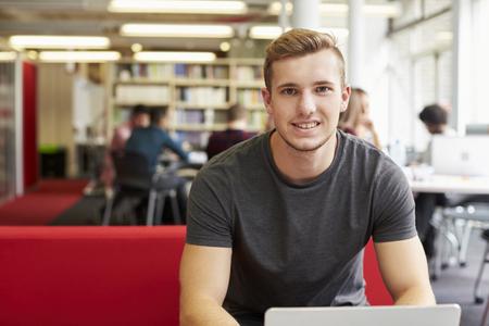 onderwijs: Portret Van Mannelijke Universitaire student die in bibliotheek