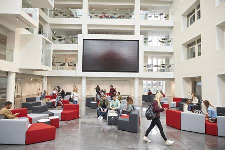 Los estudiantes en frente de la pantalla en el atrio de la universidad moderna