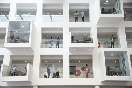 view of an atrium in a building: Students in study rooms, visible from the university lobby