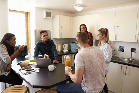 共有の宿泊施設のキッチンでリラックスした学生