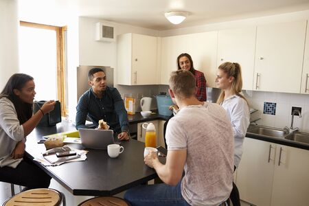 Students Relaxing In Kitchen Of Shared Accommodation Reklamní fotografie - 71304922