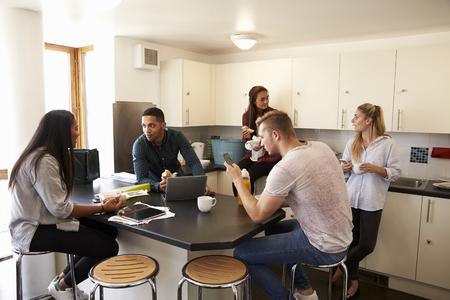 Estudantes relaxando na cozinha de alojamento compartilhado Imagens