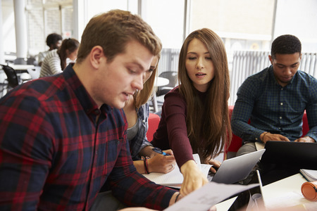 19 years old: Group Of Students In Library Collaborating On Project