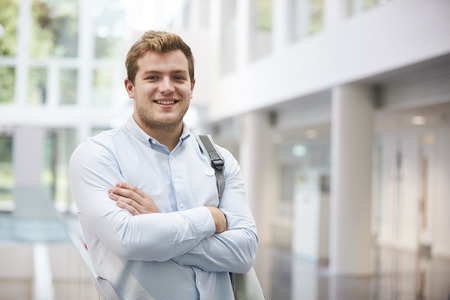 Smiling adult male student in modern university lobby Stock Photo