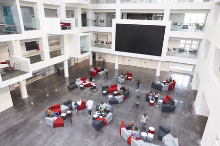 organised group: Modern university lobby atrium and glass fronted study rooms