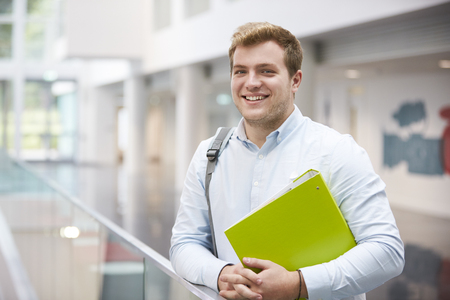 view of an atrium in a building: Smiling Caucasian male student in modern university building