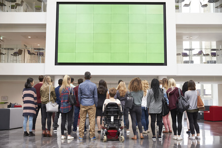 view of an atrium in a building: Students looking up at a big screen in university atrium Stock Photo