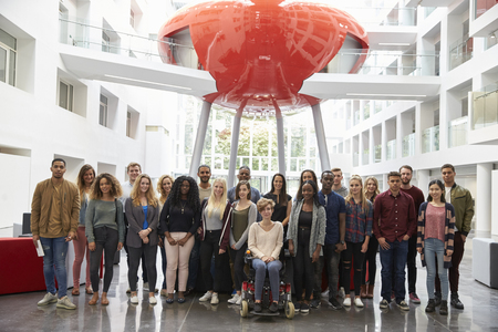 view of an atrium in a building: Students in modern university building, large group portrait