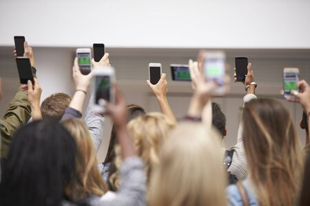 adult entertainment: Young adults with arms raised take pictures with smartphones Stock Photo