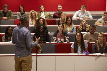 Hintere Ansicht des Mannes vorstellend zu den Studenten an einem Vorlesungsstadium