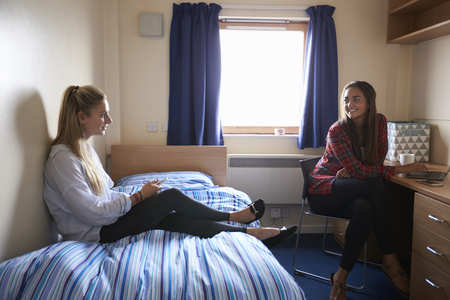 Female Students Working In Bedroom Of Campus Accommodation Stockfoto