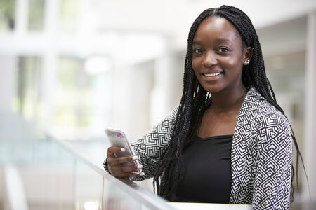 Young black female student holding phone in university foyer