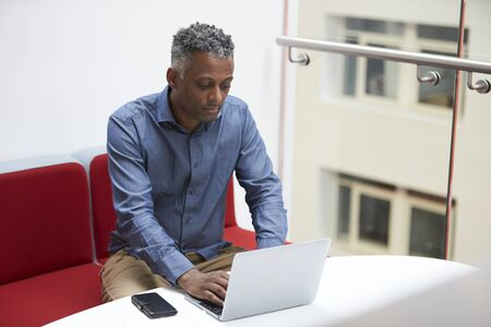 Middle aged black man uses laptop on mezzanine, elevated view Stock Photo