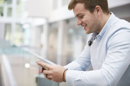 view of an atrium in a building: Adult male student using smartphone in university, close up