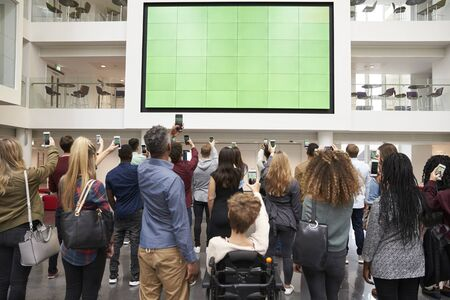 view of an atrium in a building: Students photographing big screen with phones, back view Stock Photo
