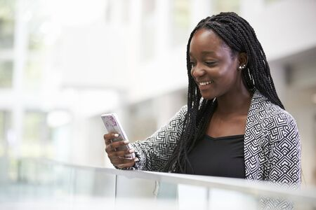 Young black female student using phone in university foyer Stock Photo