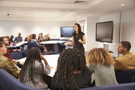 Weibliche Lehrerin, die Studenten in einem Klassenzimmer anspricht Standard-Bild
