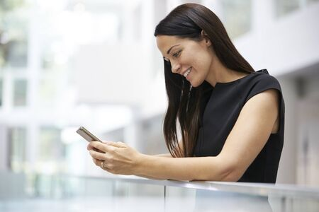 view of an atrium in a building: Young woman using smartphone in modern university interior Stock Photo