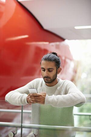 Asian male university student using smartphone, vertical Stock Photo