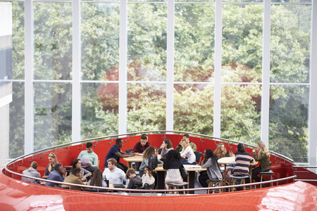 elevated walkway: Students hanging out in university mezzanine social area Stock Photo
