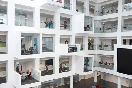view of an atrium in a building: Wide view of students in study cubicles in modern university