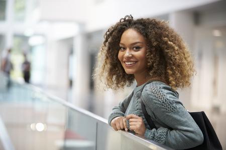 Glimlachende gemengd ras jonge vrouw naar camera kijken