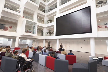 view of an atrium in a building: Students at a lecture in the atrium of a modern university