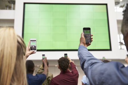 view of an atrium in a building: Students photograph screen with phones, back view, close up Stock Photo
