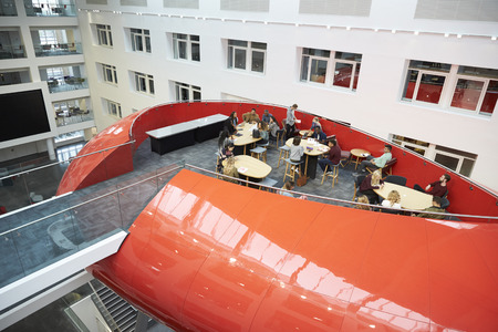 view of an atrium in a building: Students hanging out in university mezzanine social area Stock Photo