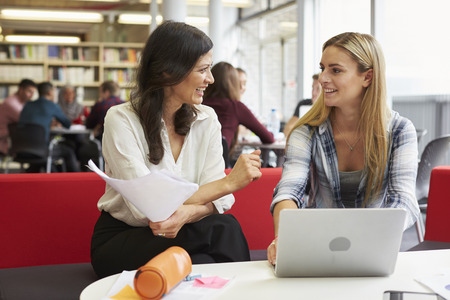 Vrouwelijke University student die in bibliotheek met Tutor