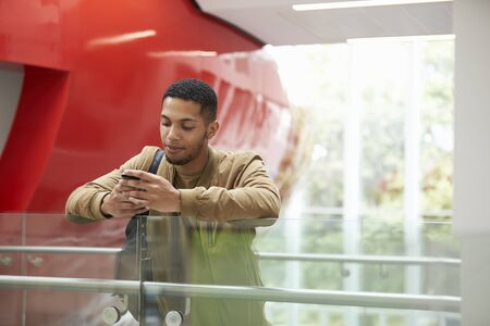 view of an atrium in a building: Male adult student using smartphone in modern university building