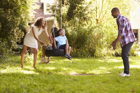 Parents Pushing Children On Tire Swing In Garden Banque d'images