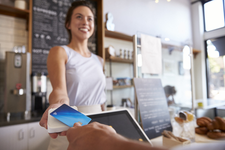 close up: Customer at coffee shop pays smiling waitress with card