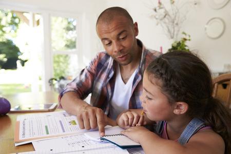 テーブルで宿題を父を助ける娘 写真素材