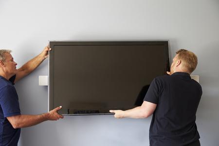 벽에 평면 스크린 텔레비전 피팅 두 남자
