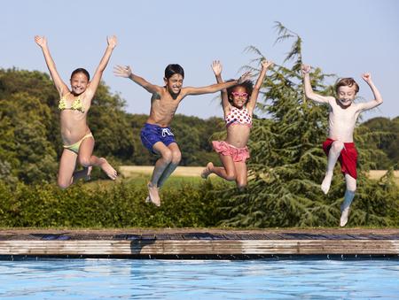 Groep Kinderen die in Openlucht Zwembad springen Stockfoto