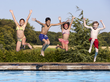Gruppo di bambini che salta in piscina all'aperto Archivio Fotografico - 71214021