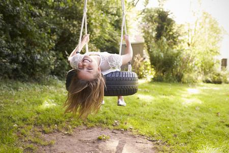 Portret van jong meisje Spelen Op Schommeling van de band in Tuin Stockfoto