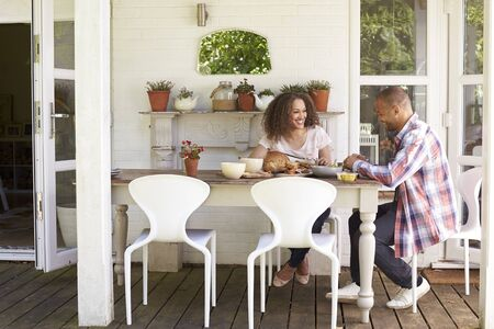 pareja comiendo: Couple At Home Eating Outdoor Meal Together