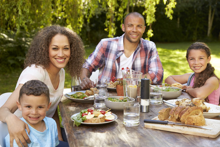 Retrato de la familia en casa comida Comer al aire libre en jardín Foto de archivo - 71214070