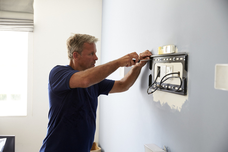 Man Fitting Bracket For Flat Screen TV Onto Wall Stock Photo