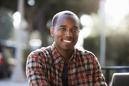 Young black man sitting outdoors, portrait Stock Photo